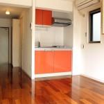 洋室とキッチン。ビビッドなオレンジがお洒落。(キッチン)